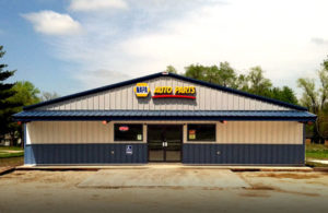 Attractive auto parts store with blue roof and wainscot trim.