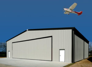 Photo of a gray steel aircraft hangar with a small plane flying overhead.