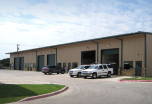 Photo of a six-bay mechanics shop in a RHINO steel garage building.