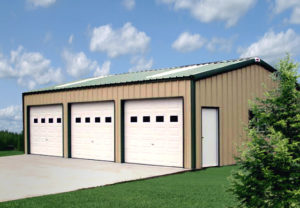 Photo of a tan three-bay metal garage with a dark green roof and trim.