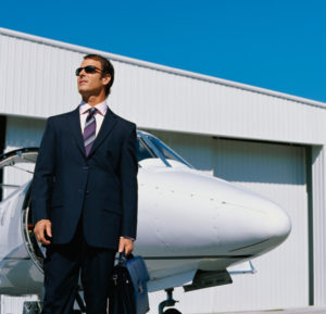 Photo of a man in a suit standing by a corporate jet in front of a steel airplane hangar.