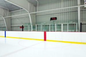 Photo of the inside of a hockey rink in a metal building.