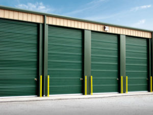 Tan self-storage units with forest green doors and trim.