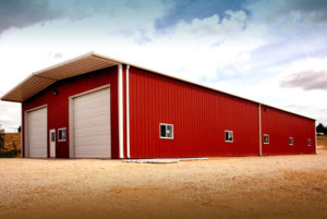 Bright red storage building with white trim and two overhead doors.