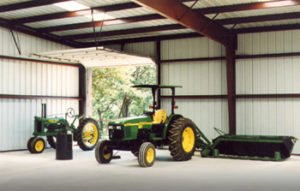 Interior of a RHINO steel barn with tractors and farm equipment inside.