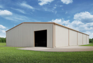 White steel farm building with tan trim and gutters.