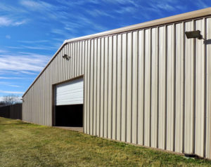 Photo of a large RHINO steel building with a single large opening and an overhead door.