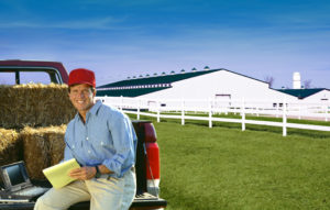 Photo of farmer sitting on truck tailgate in front of a white steel barn with a green metal roof.