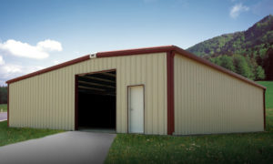 Tan RHINO metal farm building with a dark red trim and an open doorway.