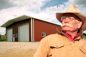 Rancher stands before a RHINO red metal barn with white trim.