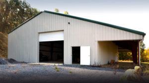 Tan metal barn with dark green metal roof.
