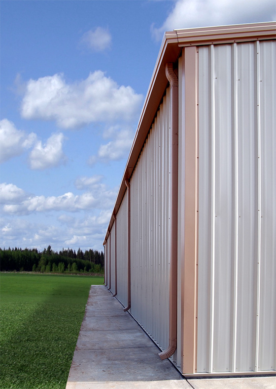 Photo of a steel building with gutters and downspouts.