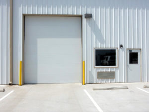 Photo of white metal building with an overhead door, entry door, and fixed glass window.